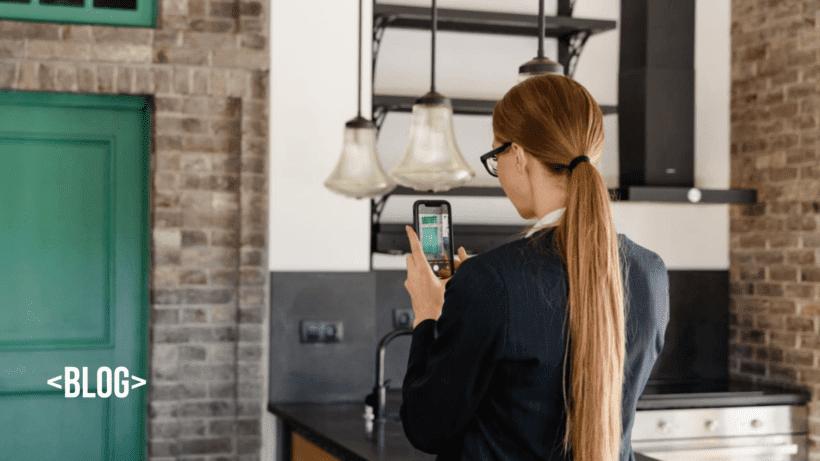 imagem descreve uma mulher segurando um celular, tirando uma foto de um imóvel. Avaliação de imóvel
